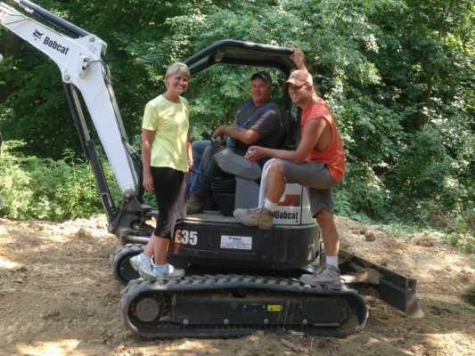 Brian Clark on his machinery with his wife and son.